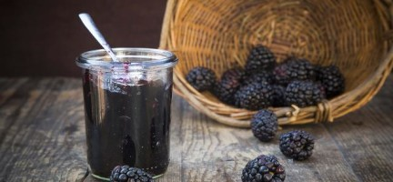 Basket of blackberries (Rubus sectio Rubus) and preserving jar of blackberriy jelly on wooden table